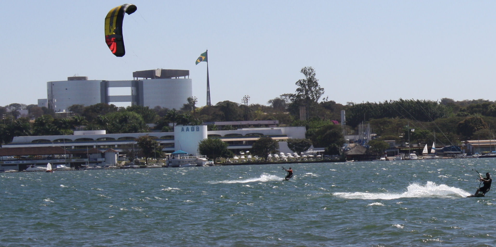 Wind surfers on Lake Paranoa in Brasilia with Brazilian flag in background